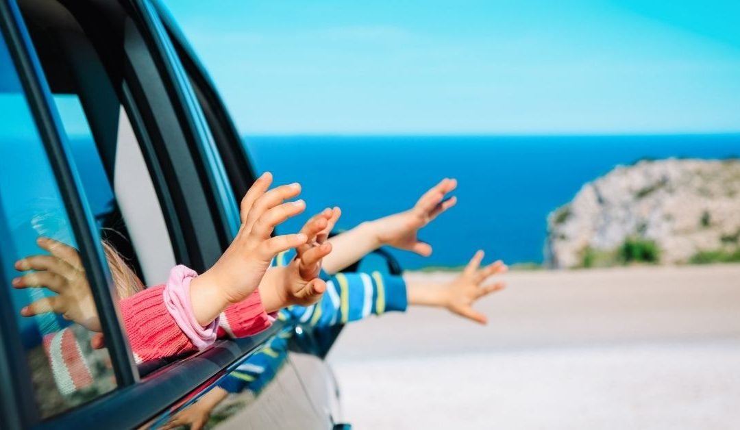 Image of kids feeling the air out the window as parents drive them somewhere.
